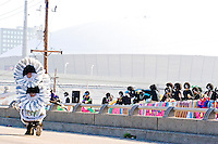 "The Krewe of Zulu watches as ""flag boy"" Ruben Jones and the rest of the Golden Comanches Mardi Gras Indians parade on the interstate to the Superdome in New Orleans on February 28, 2006."