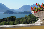 A view from Menaggio of Lake Como, Italy with Bellagio in the distance and a stone flower pot with red flowers in the foreground.