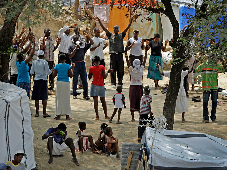 Haitians attend a prayer session during the afternoon at Haiti's only golf course. It is now home to tens of thousands survivors at the Petion-Ville Club golf course on March 3. 2010...