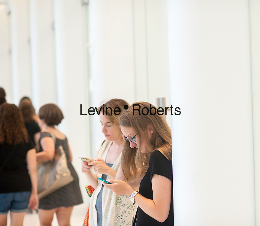 Women on their smartphones in the World Trade Center Transportation Hub, known as the Oculus, on Tuesday, August 16, 2016 during the grand opening of the retail spaces. The 350,000 square foot retail space will feature over 100 stores when they all open, including a now opened Apple Store. The mall opens almost 15 years after the World Trade Center terrorist attack.  (© Richard B. Levine)