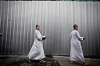 """Mae Chees clad in white robes walk silently in the early morning light, holding out their alms bowls as they go out to the neighborhood streets to collect charity. Vanished by centuries the lineage of """"Bhikkhu?nii"""" (Order of Nuns) has been brought to the ongoing Thai society's debate. White-clad thai nuns, who keep the eight precepts and have their heads and eyebrows shaved are known as the lon-existing """"mae chees"""" (low category to call the lay nuns). Females who have turned to religous life, as renunciants, live ostracized and marginalized by the Sangha (Buddhist community) and Thai society, denying them full access to the monastic life as well as rights and support from the government. Today nunhood is not recognized by any asian country belong to the Theravada Buddhist order. Most of the eight precept holders live in temples run by male abbots, at the shadow of the monks; with the exceptional existence of a few para-monastic institutions as the Sathira Dhammasathan meditation centre, where """"mae chees"""" are not allow to held a temple, but not denied to practice the spiritual life."""