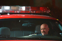 A Columbus, Ohio, fire fighter sits in a car before investigating a car fire.<br />