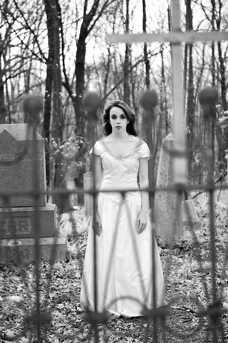 A teenage girl in a graveyard wearing a wedding dress with a Christian Cross