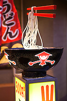 Udon is a type of thick wheat flour noodle popular in Japanese cuisine..Udon is usually served hot as noodle soup in broth in its simplest form. It is usually topped with thinly chopped scallions. Other common toppings include tempura.  A thin slice of kamaboko, a halfmoon-shaped fish cake, is often added.  The flavor of broth and topping vary from region to region. Usually, dark brown broth, made from dark soy sauce is used in eastern Japan, and light brown broth, made from light soy sauce is used in western Japan