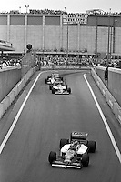 DETROIT, MI - JUNE 22: Nigel Mansell of Great Britain drives the Williams FW11/Honda RA166E ahead of teammate Nelson Piquet of Brazil in his Williams FW11/Honda RA166E and Jacques Laffite of France in the Ligier JS27/Renault EF4B during the Detroit Grand Prix FIA Formula One World Championship race on the Detroit Street Circuit in Detroit, Michigan, on June 22, 1986.