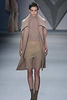 Kati Nescher walks runway in a nude Melton sleeveless wool coat with structural boucle collar and patch pocket over nude wool fencing vest and silk chiffon tank, with nude melton bermuda short from the Vera Wang Fall 2012 Vis-a-gris collection, during Mercedes-Benz Fashion Week Fall 2012 in New York.