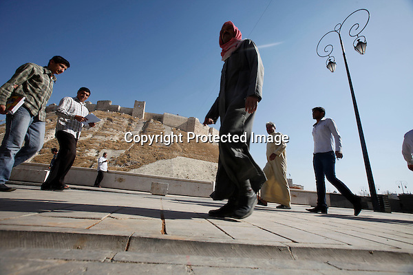 People walk at the pedstrian ring around the Aleppo castle