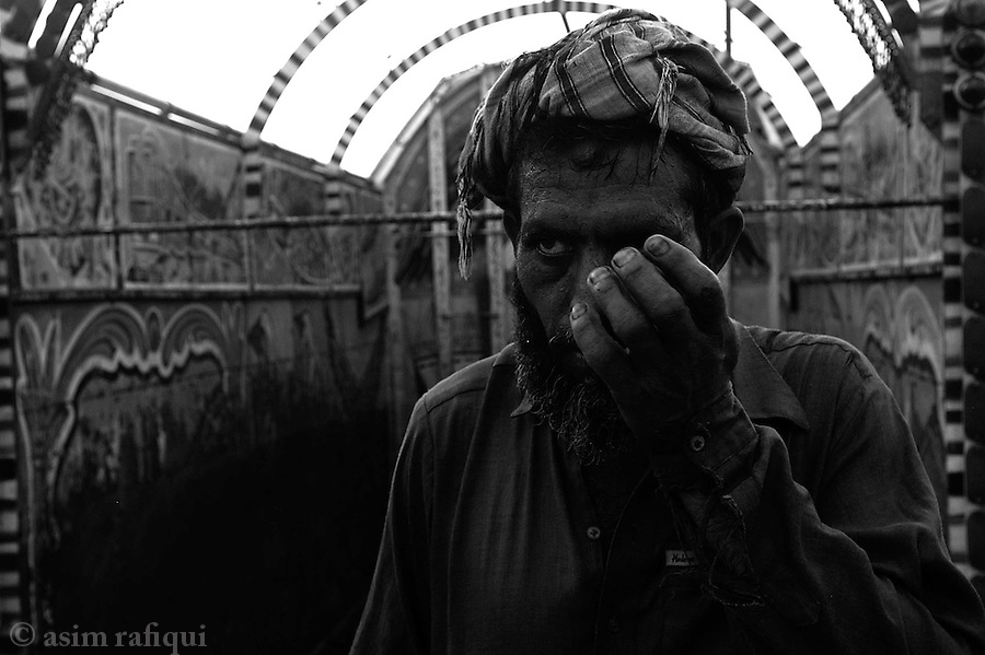 a coal worker unloading a fresh load of coal from trucks that have arrived from as far away as chakwal punjab.  jalozai, peshawar, pakistan.  september 2003&amp;#xA;&amp;#xA;copyright asim rafiqui 2003<br />