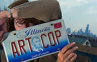 "4/6/04-Charles Osgood-Joy Neimanus, ending more than 30 years as photography professor at the School of the Art Institute of Chicago, displays her ""Art Cop"" license plate which she will take with her to her new job and home in New Mexico. (Yes she was my teacher, but I didn't know she was the owner of the vehicle when I spotted the licence plate.) ..OUTSIDE TRIBUNE CO.- NO MAGS,  NO SALES, NO INTERNET, NO TV.. Tribune Photo by Charles Osgood 00224156A sidewalks"