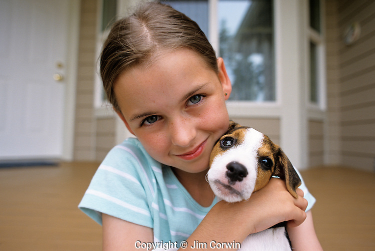 Young girl holding her puppy ( Jack Russell Terrier) smiling at camera