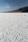 Death Valley National Park, California;  a view of the white salt crust which has formed into hexagonal honeycomb shapes from repeated freeze–thaw and evaporation cycles on the floor of Badwater Basin, in early morning sunlight, Badwater is the lowest point in North America at 282 feet below sea level