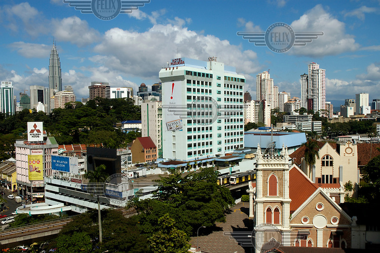 Mixed downtown architecture, ranging from the Petronas Twin Towers (rear left) to colonial era church in foreground, with LRT trains at centre.