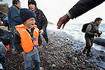 A small boy cries on a beach near Molyvos, on the Greek island of Lesbos, on October 31, 2015, as he and his family arrive on a boat from Turkey. They were received by local and international volunteers, then proceeded on their way toward western Europe. The boat was provided by Turkish traffickers to whom the refugees paid huge sums to arrive in Greece.