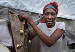 "A survivor of the January 2010 earthquake stands in the doorway of her ""tent"" home in a camp in the Bobin neighborhood of Port-au-Prince, Haiti."
