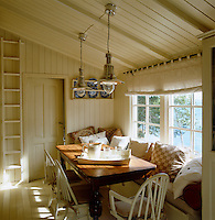 A 19th century table and old-style painted chairs furnish this wood-clad kitchen/dining area