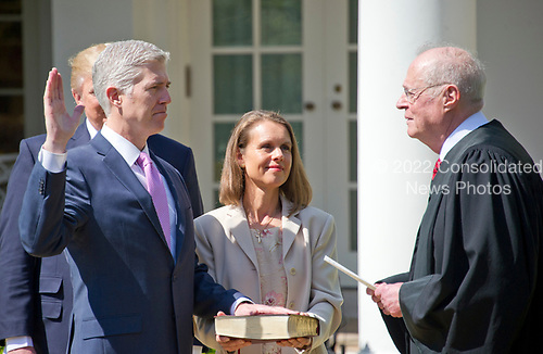 Associate Justice of the United States Supreme Court Neil Gorsuch, left, takes the Oath of Office from Associate Justice Anthony Kennedy, right, in the Rose Garden of the White House in Washington, DC on Monday, April 10, 2017.<br /> Gorsuch's wife Louise holds the Bible.<br /> Credit: Ron Sachs / CNP<br /> (RESTRICTION: NO New York or New Jersey Newspapers or newspapers within a 75 mile radius of New York City)