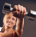 Young smiling woman doing cardio fitness workout with weights, closeup of a hand with a dumbbell