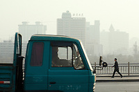 Intense traffic of the developping town of Lanzhou is one of the main sources of pollution in the city. Here along the Yellow River. China.<br /> -------<br /> Lanzhou, in the Gansu province is the most polluted cities of China and in the world's top ten for atmospheric pollution due to human activity. The town is situated between two hills along the Yellow River and the polluted clouds remains over the town. The sky is most of the time hidden by the pollution.