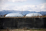 Photo shows the giant greenhouse domes at the Minamisoma Agri-Solar Park that have been built on the farmland that was affected by 2011's devastating tsunami and nuclear accident in Minamisoma, Fukushima, just 25 km from the Daiichi plant. More than 2,000 solar panels will power the  domes, inside which farmers affected by the 2011 tsunami and nuclear accident will be able to grow produce.   In the foreground is the concrete foundations of a building flattened by the tsunami..Photographer: Robert Gilhooly