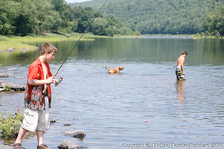 Swimmers and fishermen including Noah Rave, age 11, of Lackawaxen, PA, enjoy the scenic Upper Delaware River on a hot summer day in River Park in Lackawaxen, PA. The Upper Delaware Scenic and Recreational River, part of the National Park Service's Wild and Scenic Rivers System, stretches 73.4 miles along the New York - Pennsylvania border.<br /> <br /> Hydraulic fracturing or &quot;fracking&quot; is new method of drilling for natural gas: millions of gallons of water, sand and proprietary chemicals are pumped down a well under high pressure. The pressure fractures the shale, opening fissures so that natural gas can flow more freely. In August 2010, fracking is being widely used in the Marcellus Shale formation under Pennsylvania while New York considers a moratorium until the environmental effects can be reviewed. <br /> <br /> The 2005 Energy Policy Act exempted natural gas drilling from the Safe Drinking Water Act (plus some regulations of the Clean Water Act and Clean Air Act), and exempts companies from disclosing the chemicals used during fracking. Scientists have identified volatile organic compounds (VOCs) such as benzene, ethylbenzene, toluene, methane and xylene that have been found in contaminated drinking water near drilling sites. Other environmental concerns include surface water contamination, air pollution, forest fragmentation, plus human health problems. On the other hand, gas companies and property owners stand to earn up to one trillion dollars in profits from drilling in the Marcellus Shale.<br /> <br /> &copy; Michael Forster Rothbart<br /> www.mfrphoto.com <br /> 607-267-4893 o 607-432-5984<br /> 5 Draper St, Oneonta, NY 13820<br /> 86 Three Mile Pond Rd, Vassalboro, ME 04989<br /> info@mfrphoto.com<br /> Photo by: Michael Forster Rothbart<br /> Date: 8/2010    File#:  Canon 5D digital camera frame 68188.
