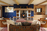 The wood burning stove is the focus of the living room, surrounded by built in seating with storage for logs