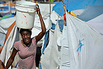 A woman carries water in a camp for homeless families set up on a golf course in Port-au-Prince, Haiti, which was ravaged by a January 12 earthquake.