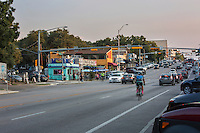 In this image a bicyclist rides up South Congress Avenue, a vibrant neighborhood full of eclectic boutiques, restaurants and live music venues - Stock Image.