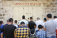 Palestinian men pray outside the Lion gate in the old city of Jerusalem on September 13, 2013.  Israeli police declared an age limit on Friday for Palestinians wanting to enter the Old City, only allowing males above the age of 45 and all females to enter, as Yom Kippur, the Jewish day of atonement, begins at sundown. Photo by Oren Nahshon