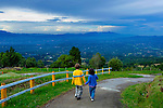 Children walk down a roadway overlooking the Central Valley And The Central Volcanic Cordillera Mountain Range In Costa Rica.