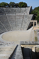 EPIDAURUS, GREECE - APRIL 15 : A detail of the cavea, the orchestra and the two paradoi of the Theatre, on April 15, 2007 in Epidaurus, Greece. The Theatre, designed by Polykleitos the Younger, was built in the late 4th century BC and extended in the Hellenistic period. It was rediscovered in 1881 and significantly restored in the 1950s.  It has the three main features of a Greek theatre: the orchestra, a sunken round stage; the skene, a raised rectangular stage; and the cavea, a raked semi-circular auditorium with radiating diazomas. To the right are the entrances to the two paradoi, or corridors, which gave the actors access to the stage. The theatre is renowned for its accoustics thanks to the symmetry of the cavea, seen here in the morning light. (Photo by Manuel Cohen)