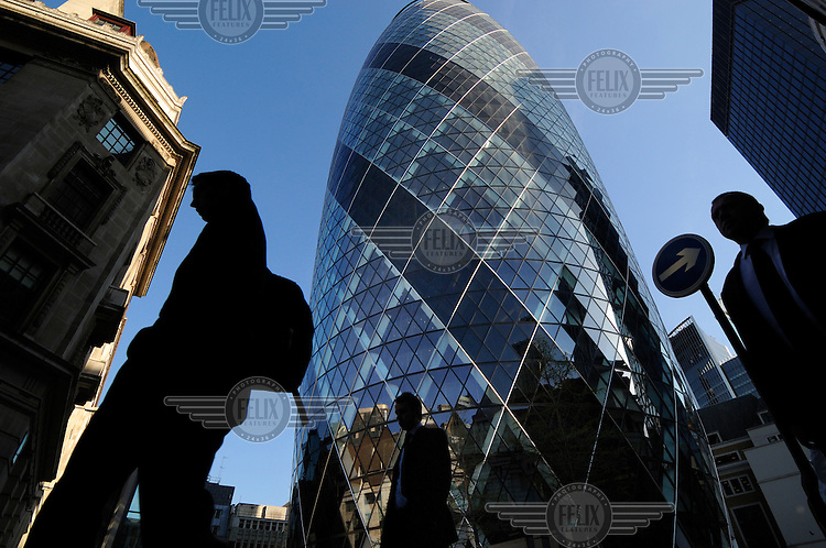Businessmen walk through the City of London close to the Swiss Re building, designed by British architect Sir Norman Foster, colloquially known as 'the Gerkin', and officially as 30 St Mary Axe.