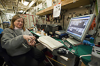 Scientist using an imaging flow cytometer, a microscope that photographs every organism as a sample of water drips by, on a research ship, Bering Sea