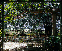 A garden table and chair are placed under a lush canopy of trees in preparationt for an al fresco lunch