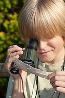 Kind, Junge nutzt Fernglas als Lupe und betrachtet eine Feder, Fernglas lässt sich umgedreht als vergrößernde Lupe verwenden