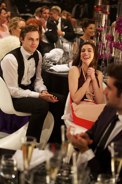 Nick Hoult and Anne Hathaway enjoy the speeches at Elton John's White Tie and Tiara Ball