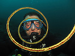 Kenting, Taiwan -- Diver seen through the spirals of a whip coral.<br />