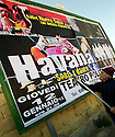 A billposter puts together several parts of a large playbill on a very windy day.