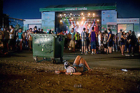 BENIC&Agrave;SSIM, SPAIN - A girl lies asleep at the rear of the audience at the Festival's main stage during a performance by English band Hot Chip...Described by some as a Mediterranean Glastonbury, the Festival Internacional de Benic&agrave;ssim (FIB) is the largest music festival outside the UK to target British visitors. In 2010, seven of the eight main headline slots were filled by English bands...A small coastal town of 13,000 inhabitants, Benic&agrave;ssim hosted some 200,000 visitors in 2009, with 40% of those believed to be coming from the UK. In 2010, attendances fell to 127,000 visitors but the percentage of UK visitors is believed to have risen.