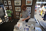 Darlene Lominick looks over art at the Double Decker Arts Festival in Oxford, Miss. on Saturday, April 28, 2012.