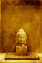 Buddha head sculpture photographed in studio with alternative post processing.