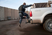 KIRKUK, IRAQ:  An Iraqi policeman climbs into the back of the police pickup truck...Security is tightened in the volatile Iraqi city of Kirkuk the day before the national elections.  Kirkuk is home to Kurds, Arabs, and Turkmen and has been so violently divided that the city could not participate in the 2005 elections.