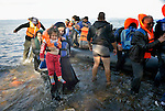 A refugee mother carries her daughter ashore on a beach near Molyvos, on the Greek island of Lesbos, on October 29, 2015, after they crossed the Aegean Sea from Turkey in a small overcrowded boat provided by Turkish traffickers to whom the refugees paid huge sums. They were received in Greece by local and international volunteers, then proceeded on their way toward western Europe.