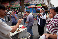 Uighur men eat melon in the Uighur district of Urumqi.