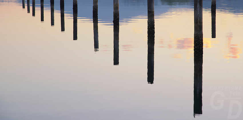 Reflections of Wooden piles at sunrise Subic Bay Philippines