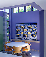 The dining room is situated under a raised roof where light floods in from an arrangement of horizontal and vertical windows and the colour-scheme was inspired by the painting propped against the wall