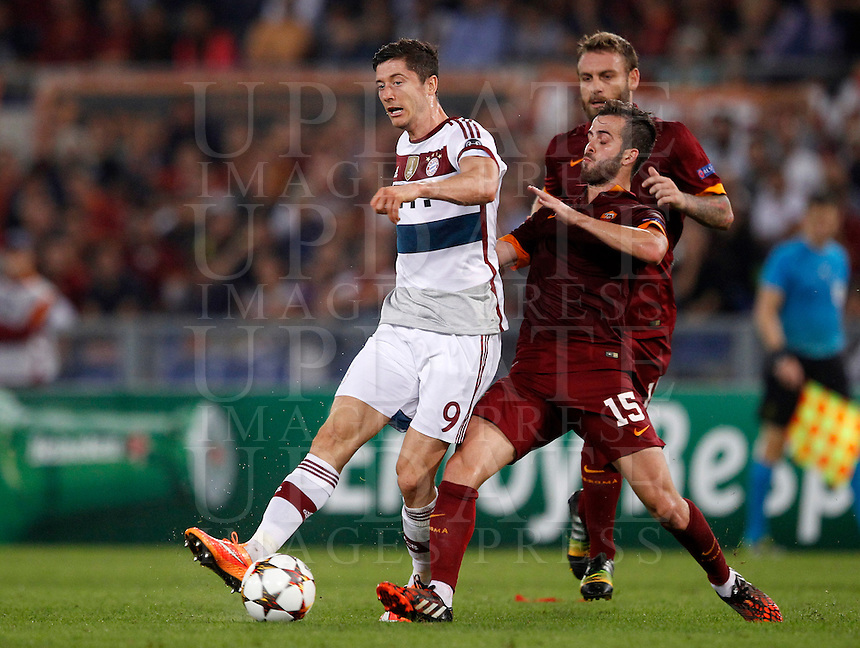 Calcio, Champions League, Gruppo E: Roma vs Bayern Monaco. Roma, stadio Olimpico, 21 ottobre 2014.<br /> Bayern&rsquo;s Robert Lewandowski, left, is challenged by Roma&rsquo;s Miralem Pjanic and Daniele De Rossi, right, during the Group E Champions League football match between AS Roma and Bayern at Rome's Olympic stadium, 21 October 2014.<br /> UPDATE IMAGES PRESS/Isabella Bonotto