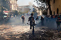 Egyptian protestors run away from tear gas canisters fired by nearby security forces during street battles November 21, 2011 near Tahrir square  in central Cairo, Egypt. Thousands of protestors demanding the military cede power to a civilian government authority clashed with Egyptian security forces for a third straight day in Cairo, with hundreds injured and at least 24 protestors killed.  (Photo by Scott Nelson)