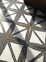 Indus stone water jet mosaic in tumbled Nero marquina, honed Thassos, and bronze.<br />