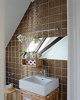 In the bathroom a wall has been lined in 1970's bronze-finish ceramic tiles with a simple oblong mirror above a ceramic wash basin