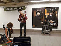 "USA. New York City. Union Square. Subway station. Two young black afro-american women are getting ready to perform live music. A billboard on the wall for a new tv program ""Boardwalk Empire"" on the pay-per view television HBO. Mosaic tiles on wall. 22.10.2011 © 2011 Didier Ruef"